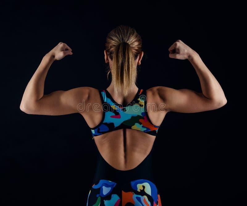 Νέο θηλυκό bodybuilder με το τέλειο ισχυρό μυϊκό σώμα που φορά sportswear την τοποθέτηση φορμών γυμναστικής στο μαύρο υπόβαθρο απ στοκ φωτογραφία με δικαίωμα ελεύθερης χρήσης
