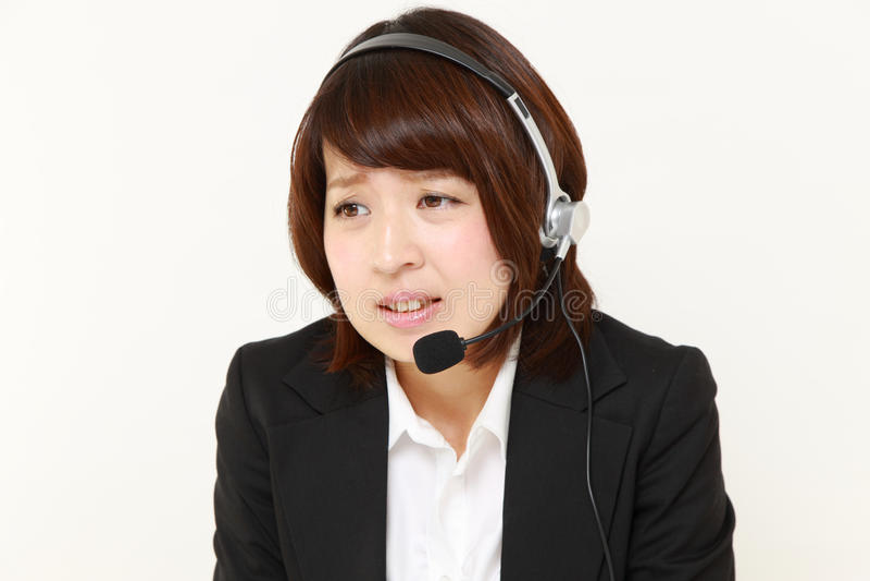 Νέο ιαπωνικό τηλεφωνικό κέντρο businesswomanof που περιπλέκεται σε ένα τηλέφωνο καταγγελίας στοκ εικόνα