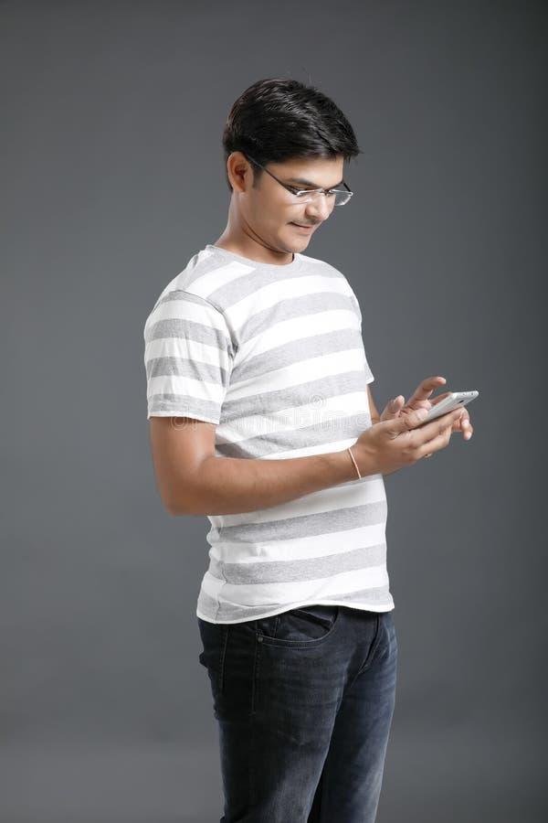 Νέο ινδικό άτομο που κρατά κινητό διαθέσιμο στοκ εικόνες