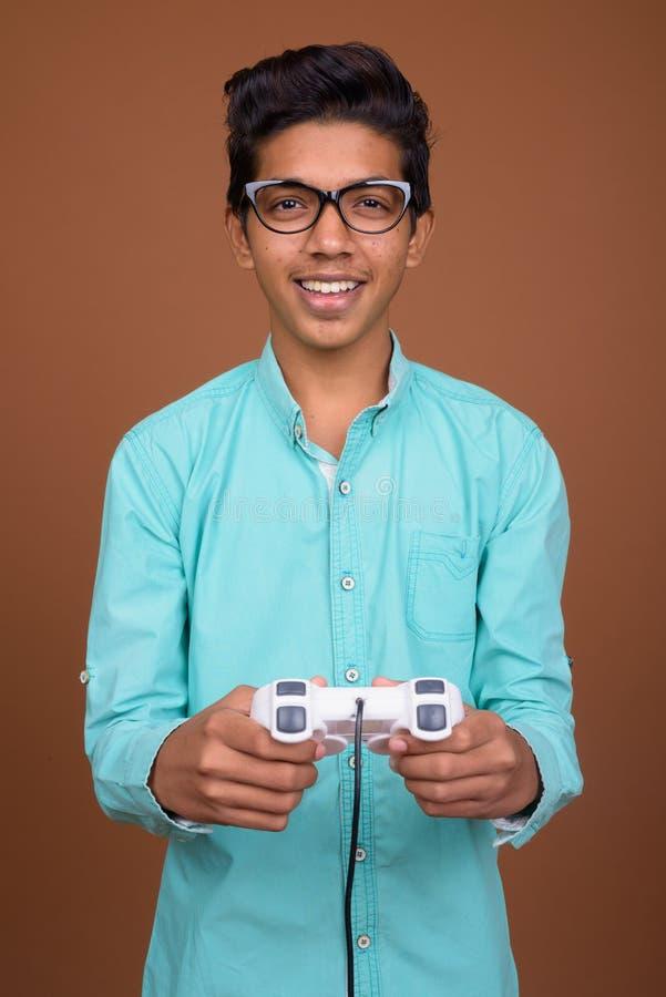 Νέο ινδικό αγόρι που φορά το μπλε πουκάμισο που φαίνεται έξυπνο ενάντια σε καφετή στοκ φωτογραφία