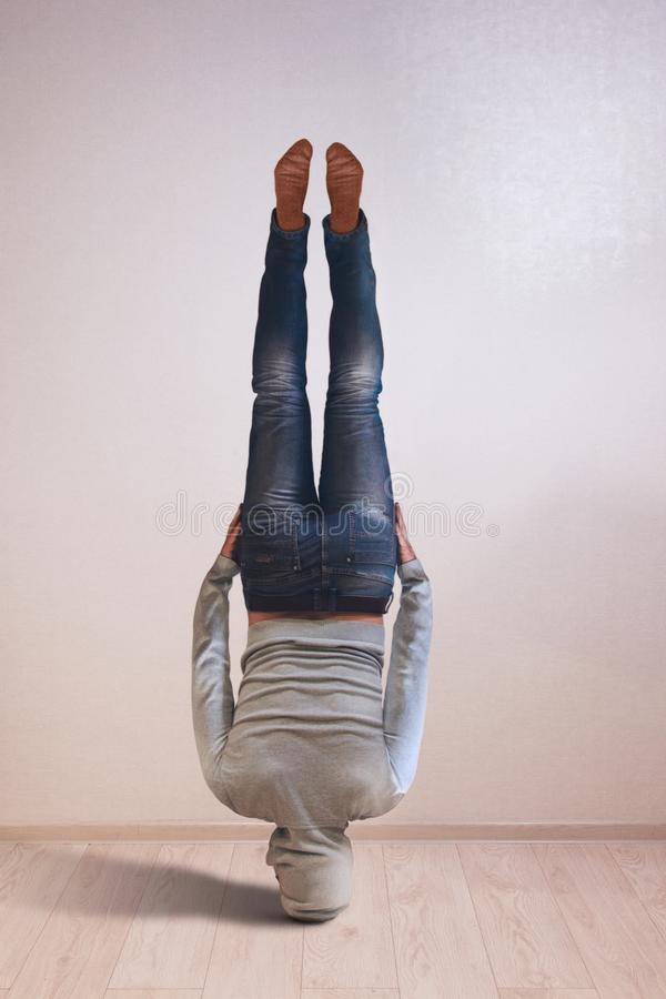 Νέο ισχυρό άτομο που στέκεται στο κεφάλι στοκ εικόνα με δικαίωμα ελεύθερης χρήσης