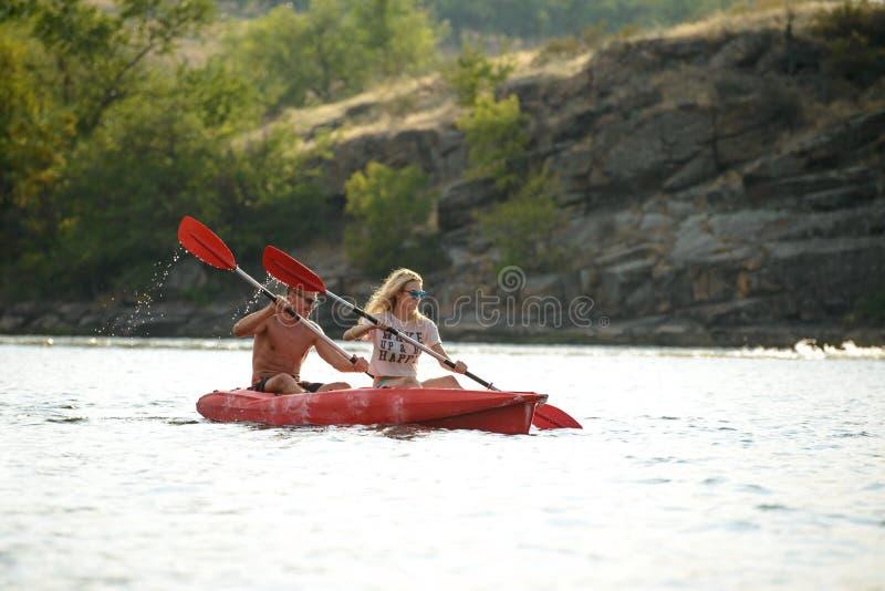 Νέο καγιάκ κωπηλασίας ζεύγους στον όμορφο ποταμό ή λίμνη το βράδυ στοκ εικόνα
