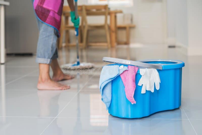 Νέο καθαρίζοντας πάτωμα γυναικών με τη σφουγγαρίστρα και τον κάδο στοκ εικόνες
