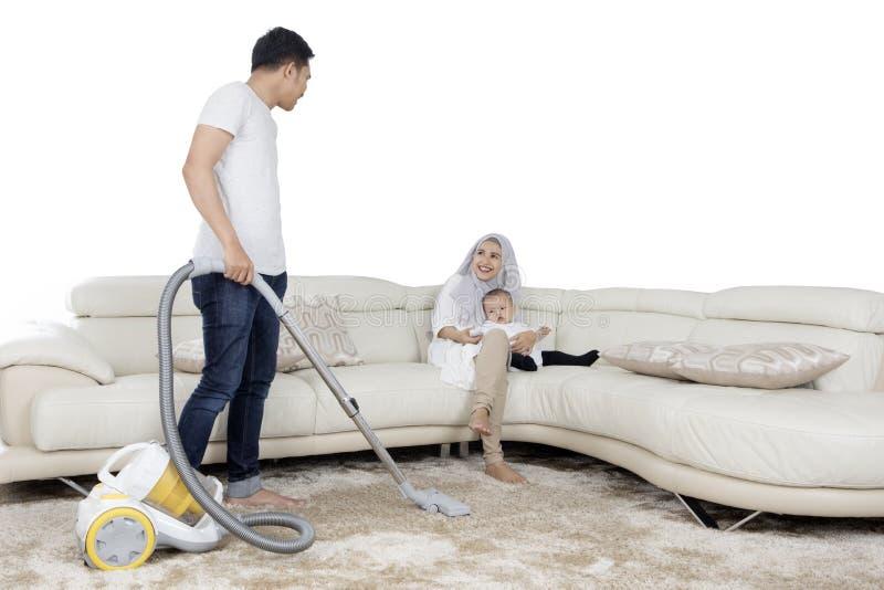 Νέο καθαρίζοντας χαλί συζύγων με την ηλεκτρική σκούπα στοκ φωτογραφία με δικαίωμα ελεύθερης χρήσης
