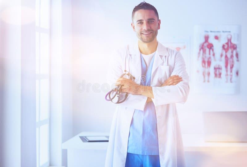 Νέο και βέβαιο αρσενικό πορτρέτο γιατρών που στέκεται σε ιατρικό μακριά στοκ εικόνα με δικαίωμα ελεύθερης χρήσης