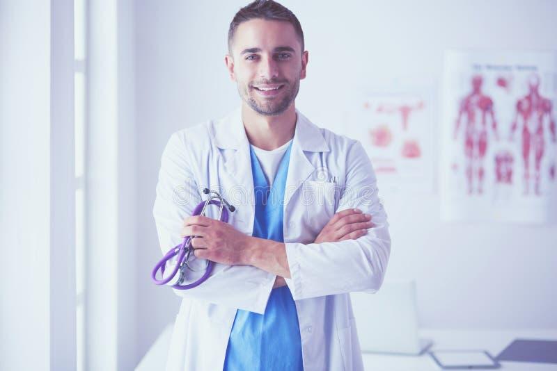 Νέο και βέβαιο αρσενικό πορτρέτο γιατρών που στέκεται στο ιατρικό γραφείο στοκ φωτογραφία