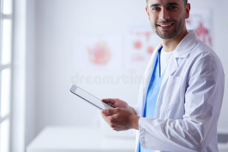 Νέο και βέβαιο αρσενικό πορτρέτο γιατρών που στέκεται στο ιατρικό γραφείο στοκ εικόνες