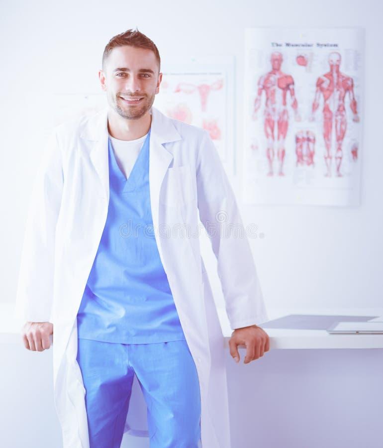 Νέο και βέβαιο αρσενικό πορτρέτο γιατρών που στέκεται στο ιατρικό γραφείο στοκ φωτογραφία με δικαίωμα ελεύθερης χρήσης
