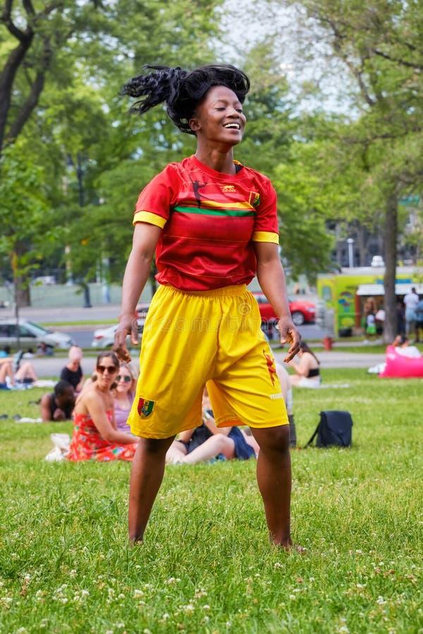 Νέο και γοητευτικό αμερικανικό θηλυκό Afro με ένα κόκκινο Τζέρσεϋ και κίτρινα σορτς που χορεύουν στη χλόη του βασιλικού πάρκου υπ στοκ εικόνες με δικαίωμα ελεύθερης χρήσης