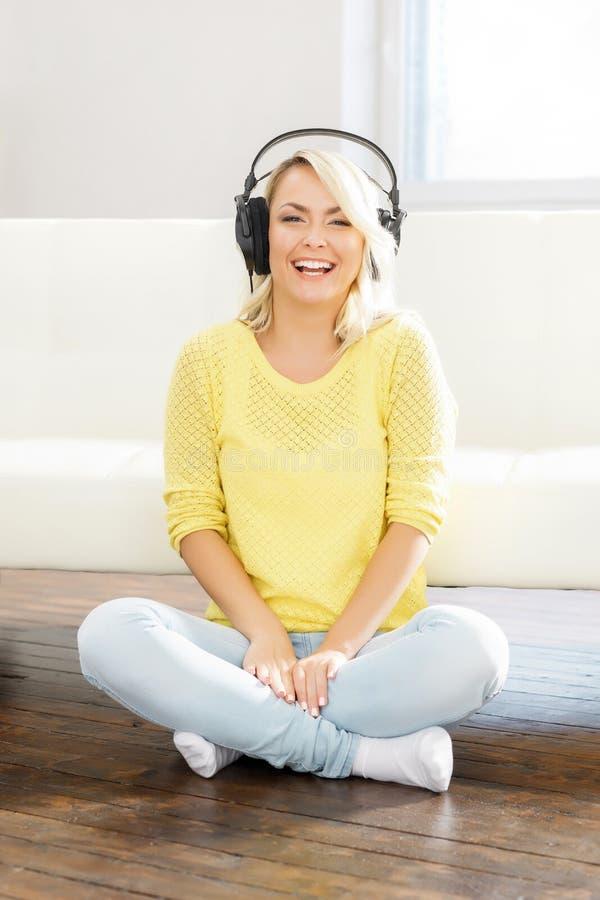Νέο και όμορφο έφηβη που ακούει τη μουσική στο σπίτι στοκ φωτογραφία