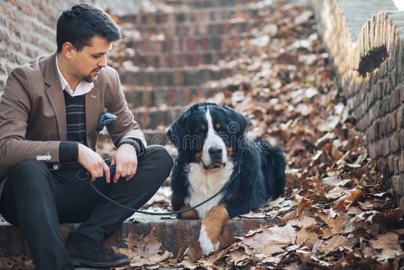 Νέο και hansome άτομο με το σκυλί του στοκ εικόνες