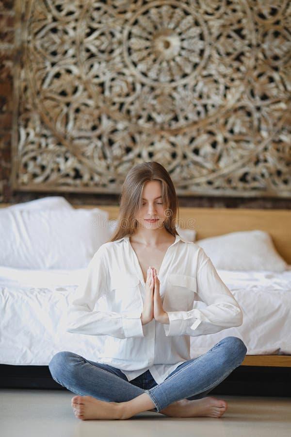 Νέο καλό κορίτσι που κάνει τη γιόγκα στο σπίτι στο πάτωμα στοκ εικόνα