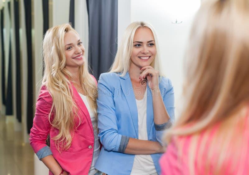 Νέο κατάστημα μόδας δωματίων συναρμολογήσεων γυναικών δύο που φαίνεται καθρέφτης, ευτυχή χαμογελώντας ξανθά κορίτσια που δοκιμάζε στοκ εικόνες