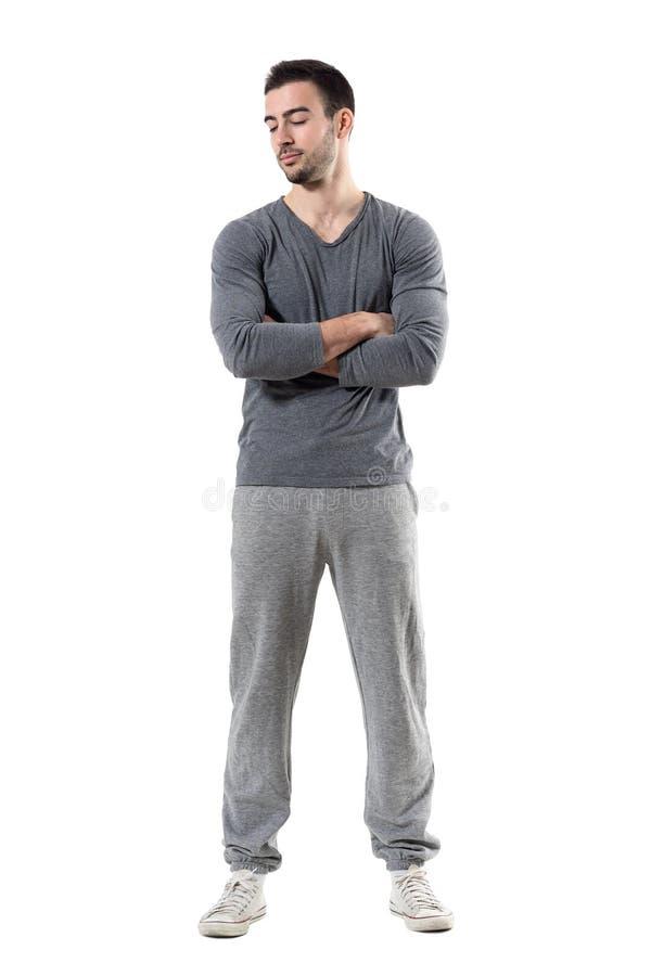 Νέο κατάλληλο μυϊκό φίλαθλο άτομο με τα διασχισμένα όπλα που κοιτάζει κάτω στοκ εικόνες
