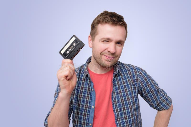 Νέο καυκάσιο άτομο με την ακουστική ταινία κασετών smilinf στο μπλε υπόβαθρο στοκ φωτογραφίες με δικαίωμα ελεύθερης χρήσης