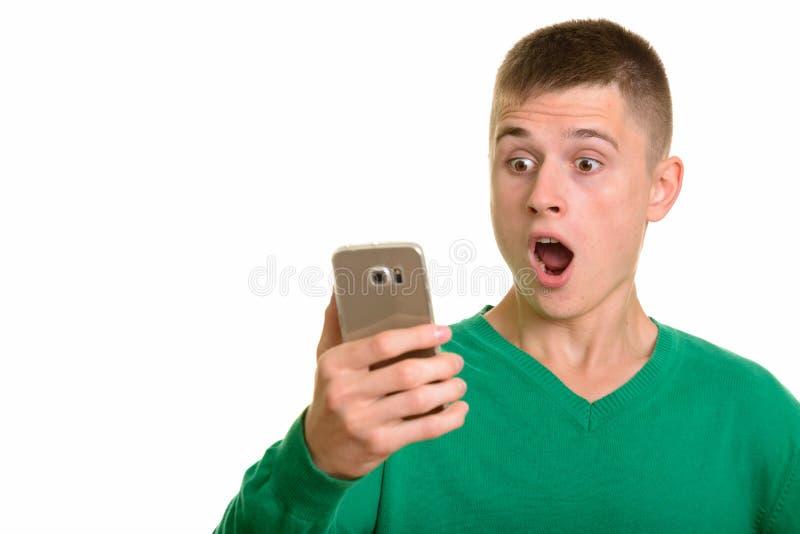 Νέο καυκάσιο άτομο που κρατά το κινητό τηλέφωνο έκπληκτος στοκ φωτογραφία με δικαίωμα ελεύθερης χρήσης