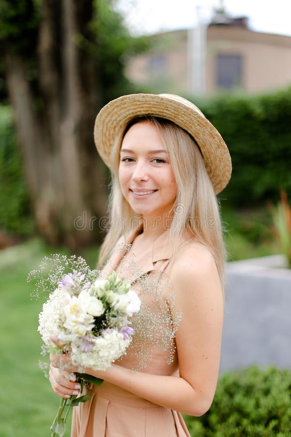 Νέο καυκάσιο κορίτσι που στέκεται στο yeard με την ανθοδέσμη των λουλουδιών και που φορά το καπέλο στοκ εικόνες