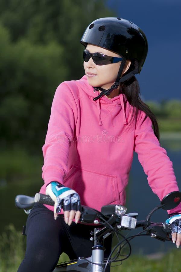 Νέο καυκάσιο grl στο οδηγώντας ποδήλατο κρανών υπαίθριο στοκ εικόνες