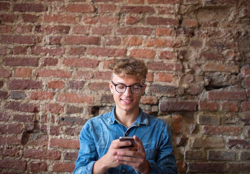 Νέο κείμενο δακτυλογράφησης σπουδαστών ατόμων χαμόγελου σε Διαδίκτυο μέσω του σύγχρονου κινητού τηλεφώνου στοκ εικόνα