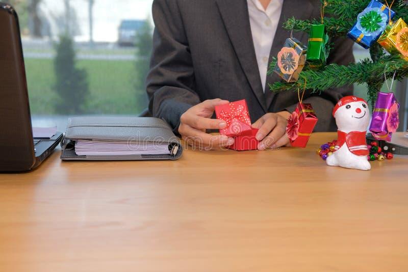 νέο κιβώτιο δώρων έτους Χριστουγέννων ανοίγματος επιχειρηματιών στον εργασιακό χώρο στοκ εικόνα