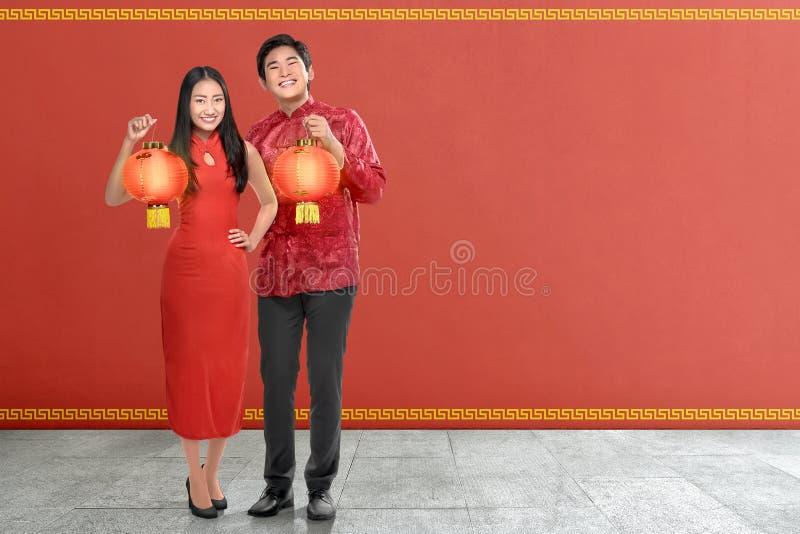 Νέο κινεζικό ζεύγος με το παραδοσιακό φόρεμα που κρατά τα κόκκινα φανάρια στοκ φωτογραφία με δικαίωμα ελεύθερης χρήσης