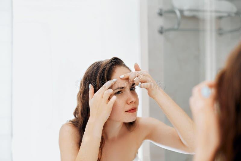 Νέο κοίταγμα γυναικών και ακμή συμπιέσεων σε ένα πρόσωπο μπροστά από τον καθρέφτη Άσχημο κορίτσι δερμάτων προβλήματος, κορίτσι εφ στοκ εικόνες