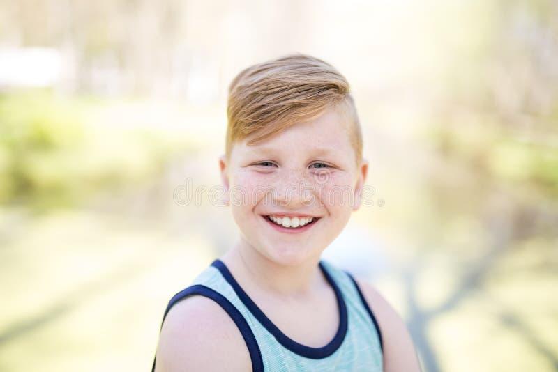 Νέο κοκκινομάλλες αγόρι που παίζει έξω στοκ εικόνες