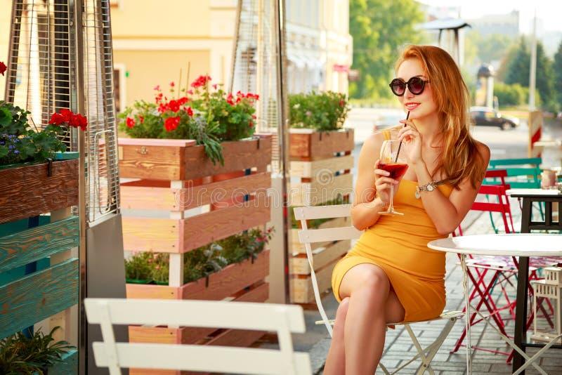Νέο κοκτέιλ κατανάλωσης γυναικών μόδας σε έναν καφέ στοκ φωτογραφίες