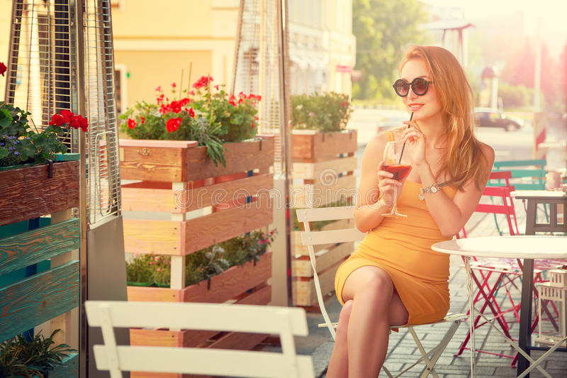 Νέο κοκτέιλ κατανάλωσης γυναικών μόδας σε έναν καφέ στοκ φωτογραφίες με δικαίωμα ελεύθερης χρήσης