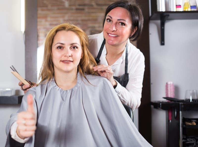 Νέο κορίτσι ευχαριστημένο από το μοντέρνο κούρεμά της και haircutter στοκ φωτογραφία με δικαίωμα ελεύθερης χρήσης