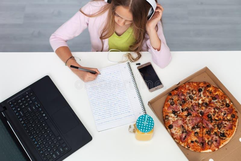 Νέο κορίτσι εφήβων που εργάζεται σε μια συνεδρίαση προγράμματος στο γραφείο της στοκ εικόνες