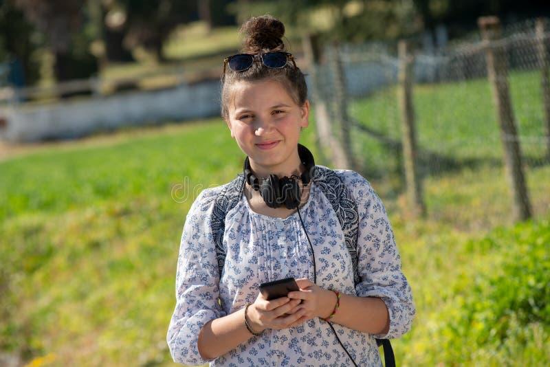 Νέο κορίτσι εφήβων που περιμένει το σχολικό λεωφορείο και που χρησιμοποιεί το smartphone της στοκ φωτογραφία