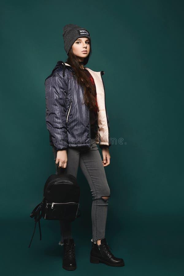 Νέο κορίτσι εφήβων brunette, στο σακάκι και το καπέλο με μια τσάντα, στάσεις ολόκληρες πέρα από το σκούρο πράσινο υπόβαθρο, στοκ εικόνες