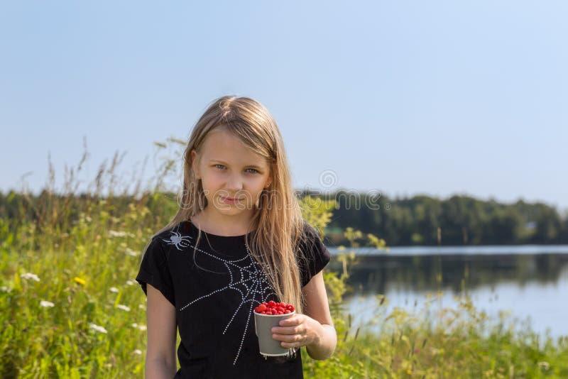 Νέο κορίτσι με άγριες φράουλες στη λίμνη στοκ φωτογραφίες