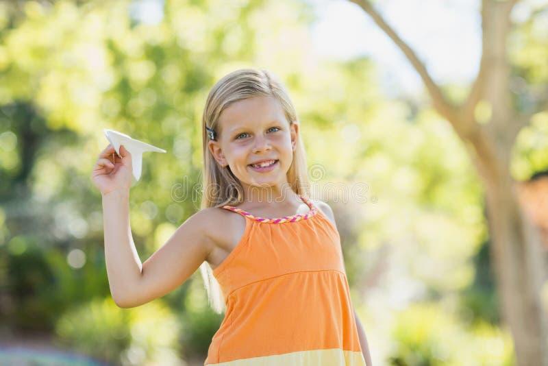 Νέο κορίτσι με ένα αεροπλάνο εγγράφου στο πάρκο στοκ φωτογραφία