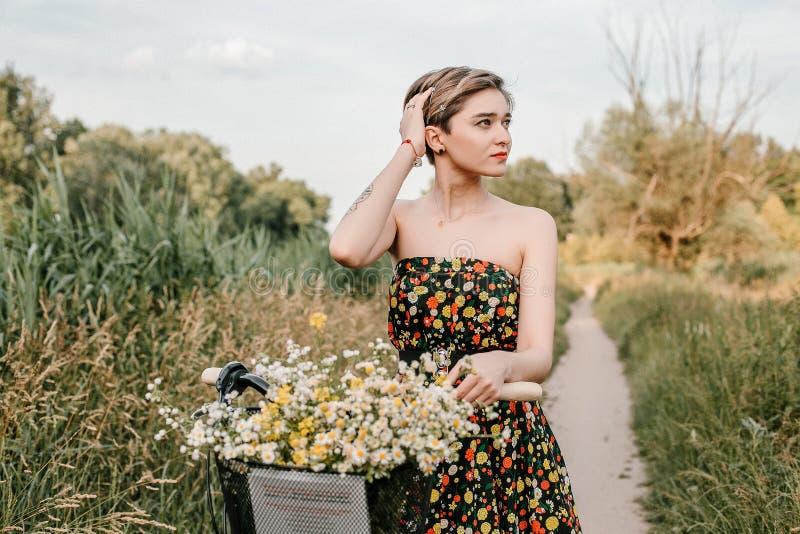 Νέο κορίτσι με ένα ποδήλατο Όμορφα γυναίκα και λουλούδια στο καλάθι Περπάτημα στη φύση E στοκ φωτογραφίες