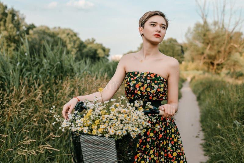 Νέο κορίτσι με ένα ποδήλατο Όμορφα γυναίκα και λουλούδια στο καλάθι Περπάτημα στη φύση E στοκ εικόνες