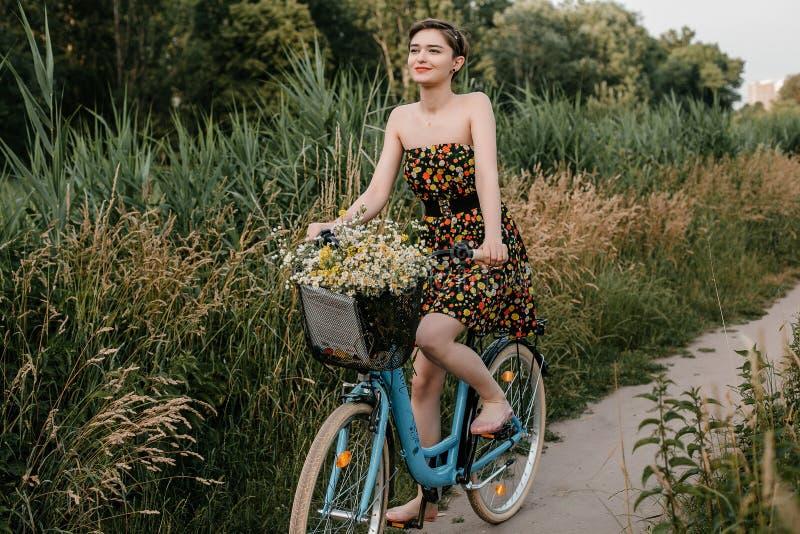 Νέο κορίτσι με ένα ποδήλατο Όμορφα γυναίκα και λουλούδια στο καλάθι Περπάτημα στη φύση E στοκ φωτογραφία με δικαίωμα ελεύθερης χρήσης