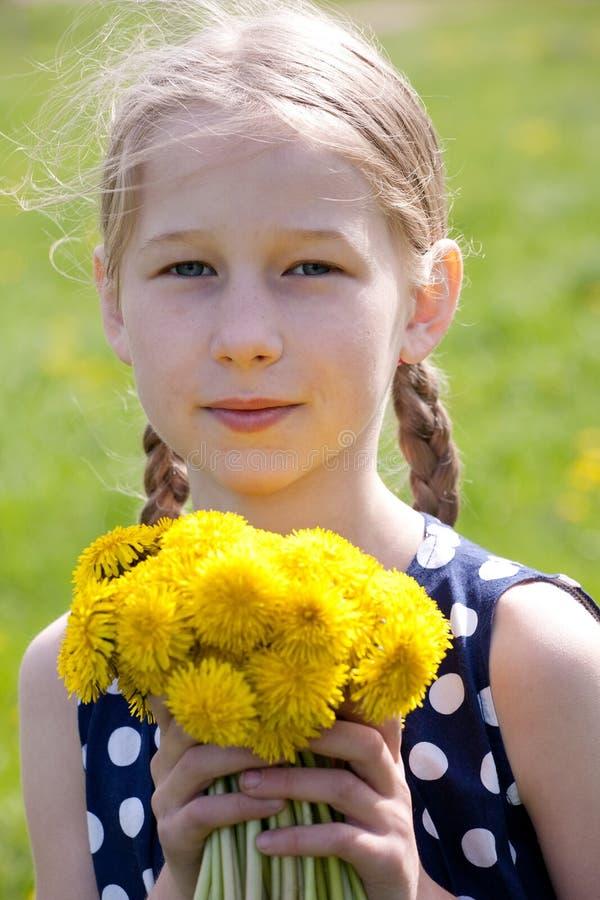 Νέο κορίτσι με μια δέσμη των κίτρινων πικραλίδων στοκ εικόνες