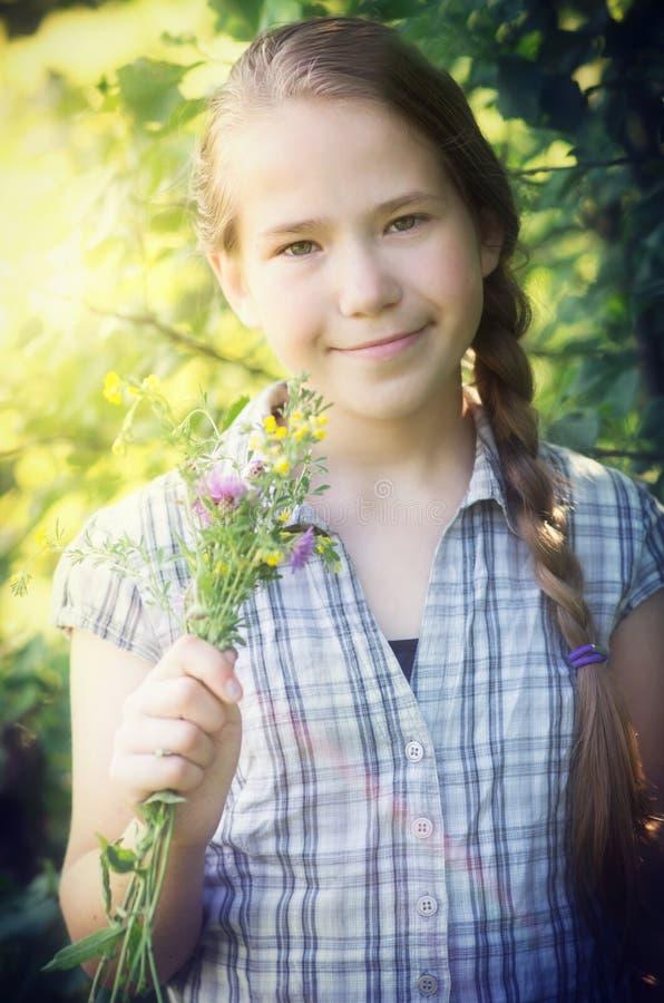 Νέο κορίτσι με τα άγρια λουλούδια στοκ εικόνα