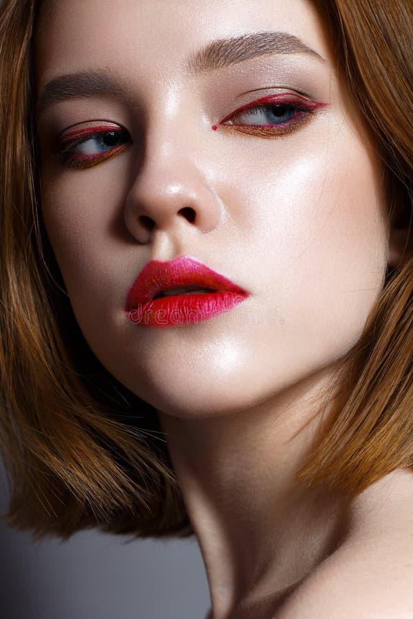 Νέο κορίτσι με τα κόκκινα χείλια και τα κόκκινα βέλη μπροστά από τα μάτια Όμορφο πρότυπο με το nude και λάμποντας δέρμα makeup Φω στοκ εικόνες