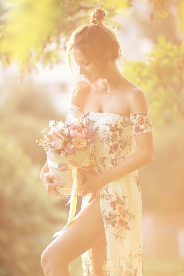 Νέο κορίτσι με τα λουλούδια στην τοποθέτηση θερινών καπέλων στον τομέα στοκ φωτογραφία