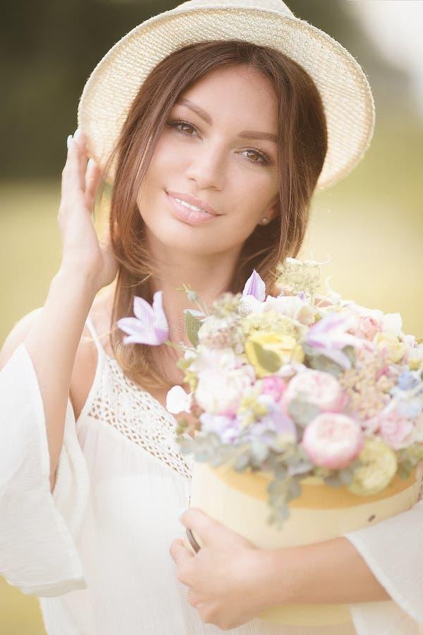 Νέο κορίτσι με τα λουλούδια στην τοποθέτηση θερινών καπέλων στον τομέα στοκ εικόνες