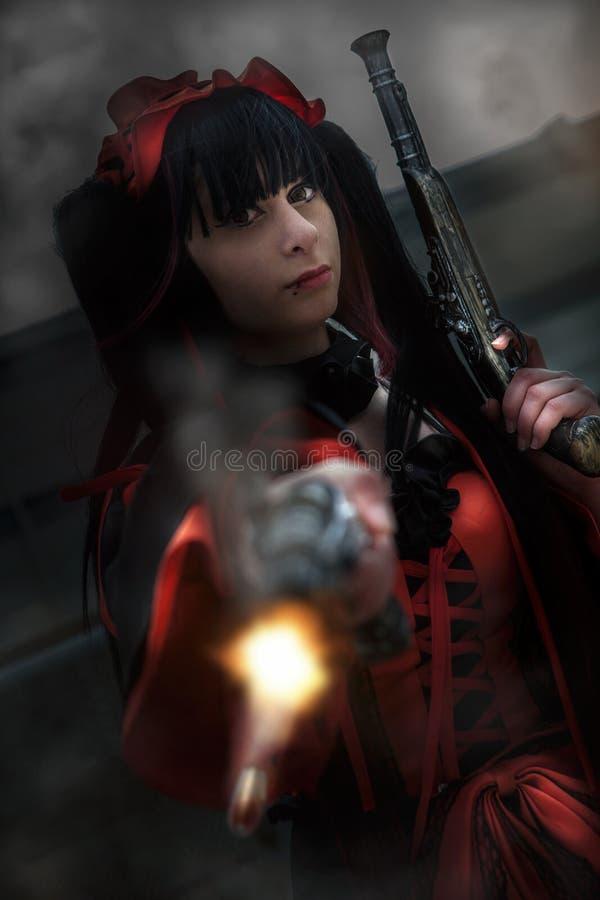 Νέο κορίτσι με τα πυροβόλα όπλα, φόρεμα περιόδου Πυρκαγιά ενός πυροβολισμού στοκ φωτογραφία με δικαίωμα ελεύθερης χρήσης
