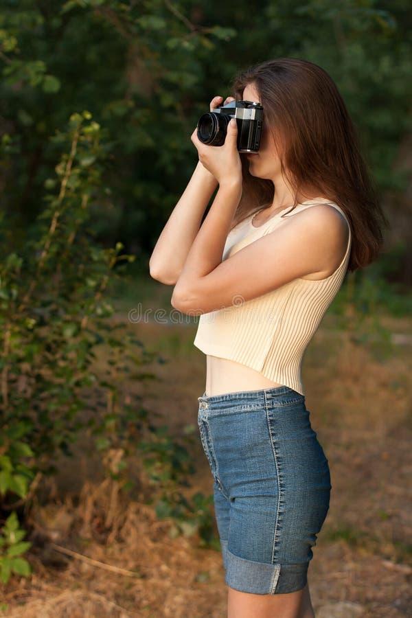 Νέο κορίτσι με την αναδρομική κάμερα φωτογραφιών στοκ εικόνα με δικαίωμα ελεύθερης χρήσης