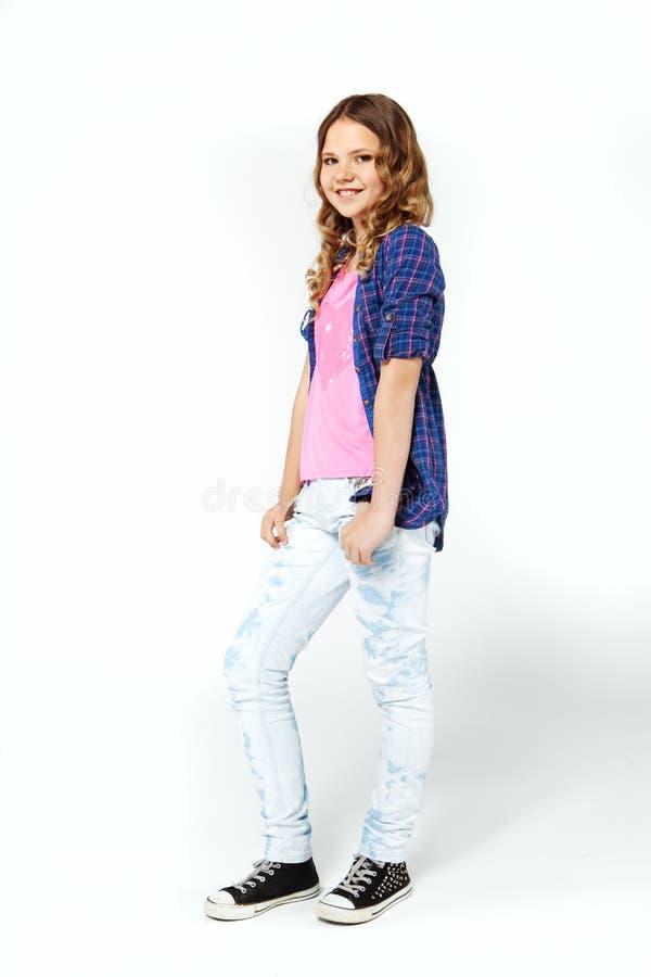 Νέο κορίτσι με τη μακριά σγουρή τρίχα που φορά το πουκάμισο και τα τζιν καρό στοκ φωτογραφία με δικαίωμα ελεύθερης χρήσης