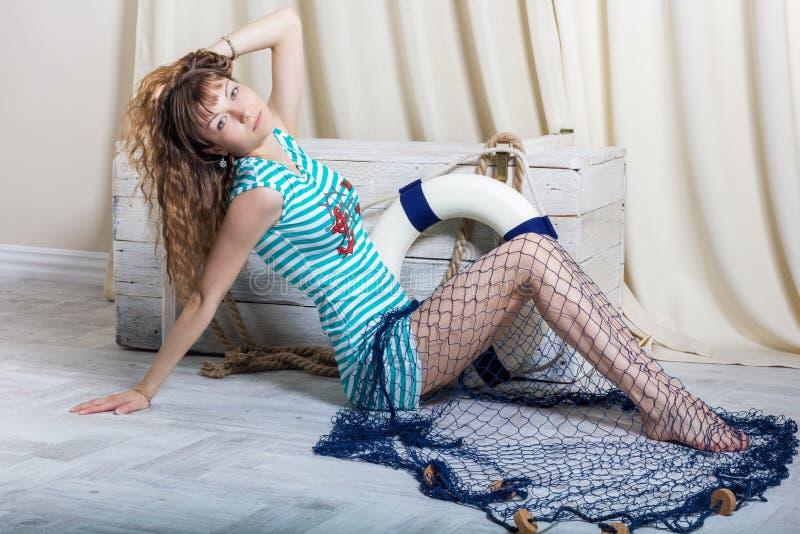 Νέο κορίτσι με τη συνεδρίαση δικτύων θάλασσας στο πάτωμα στοκ εικόνες