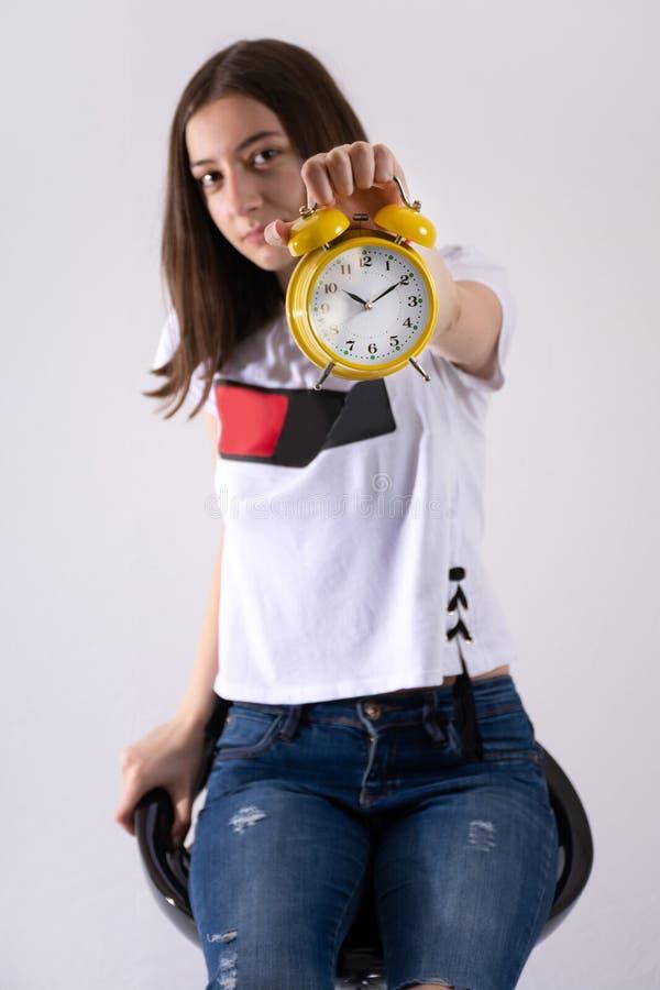 Νέο κορίτσι με τον αναδρομικό διαθέσιμο παρουσιάζοντας χρόνο ρολογιών στο κίτρινο ρολόι που απομονώνεται στο άσπρο υπόβαθρο στοκ εικόνες με δικαίωμα ελεύθερης χρήσης