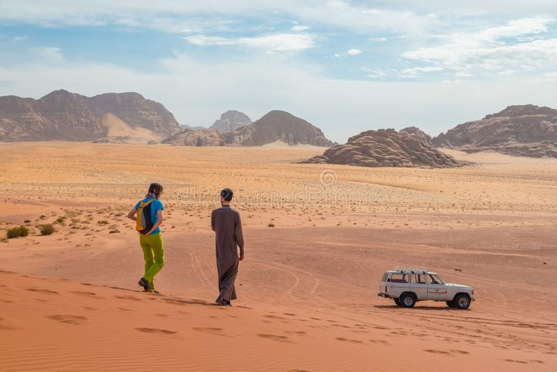 Νέο κορίτσι με το βεδουίνο τοπικό οδηγό σχετικά με έναν γύρο τζιπ σε μια απέραντη Wadi έρημο άμμου ρουμιού κόκκινη, Μέση Ανατολή, στοκ εικόνα