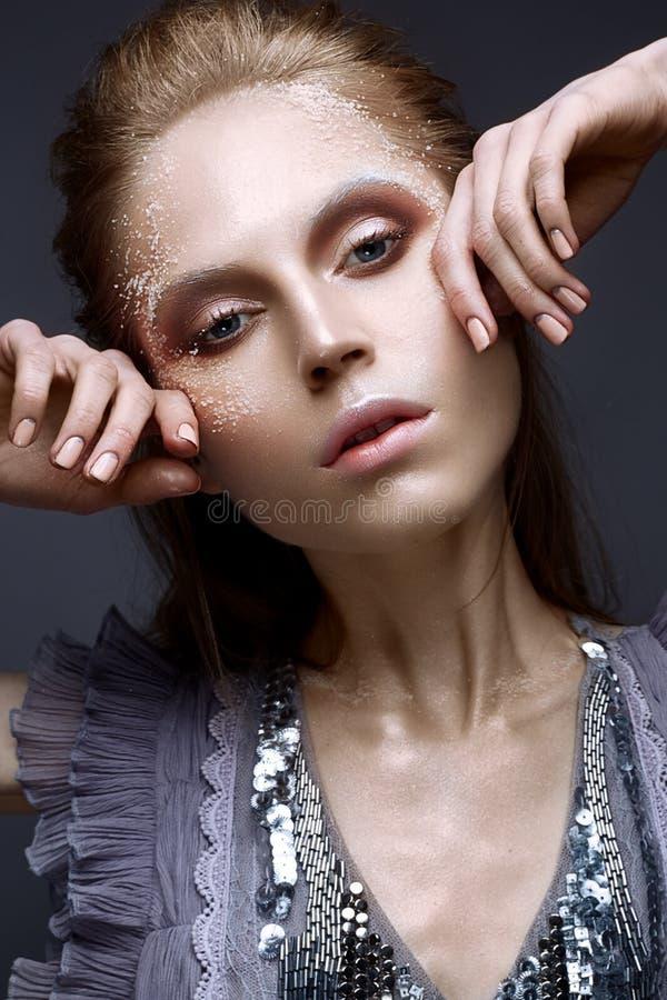 Νέο κορίτσι με το δημιουργικές makeup και τις συστάσεις στο πρόσωπό της Όμορφο πρότυπο σε ένα ιώδες φόρεμα με τα σπινθηρίσματα στοκ φωτογραφία με δικαίωμα ελεύθερης χρήσης